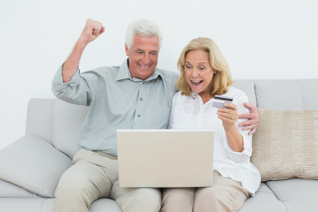Cheerful senior couple doing online shopping through laptop and